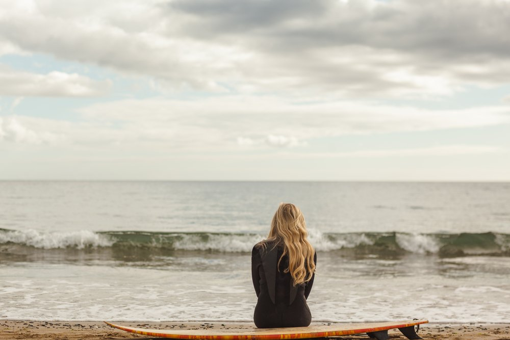 Rear view of a young blond in wet suit with surfboard at the beach-1