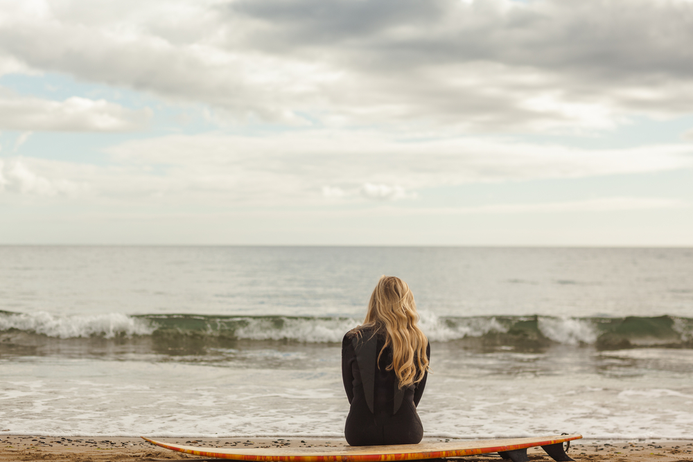 Rear view of a young blond in wet suit with surfboard at the beach